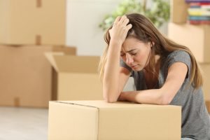 woman stressed with moving boxes
