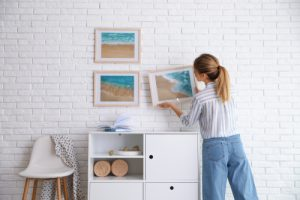 woman hanging painting on a wall