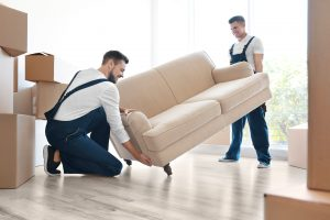 Professional Movers helping move out a couch